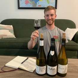 Greg Bothwell sits behind a coffee table, which holds three bottles of wine and his notebook. He is smiling and holding a glass of red wine